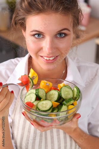 canvas print picture Young woman eating fresh salad in modern kitchen