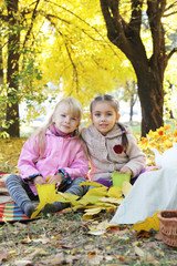 Four year girls sitting under autumn leaves
