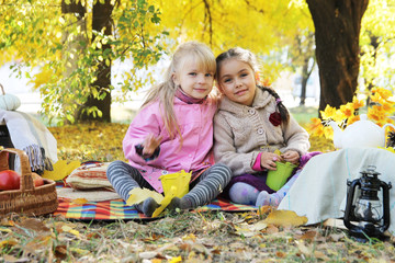Two four year girls sitting under autumn leaves