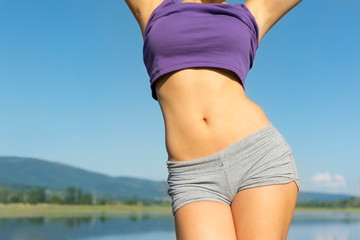 Closeup of young fit woman's belly outdoors in summer