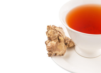 Ginger root and a cup of tea over white background