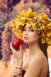 Beautiful young woman with yellow autumn wreath and apple