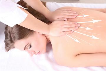 Back massage. Beautiful young woman having back massage in spa