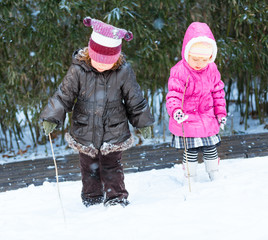 Adorable Little Girls Playing in the Snow Together