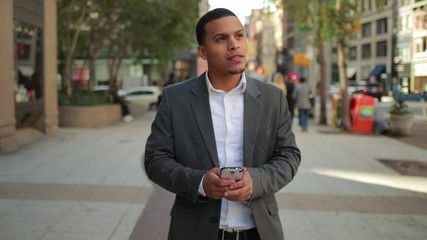Young African American black Latino man walking texting