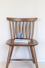 Wooden chair with coffee and book