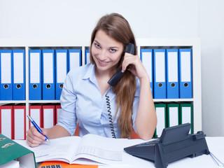 Frau mit langen blonden Haaren im Büro am Telefon