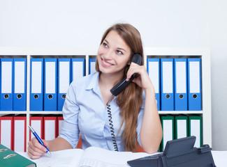 Lachende Frau mit langen blonden Haaren im Büro am Telefon