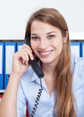 Frau mit langen blonden Haaren spricht im Büro am Telefon