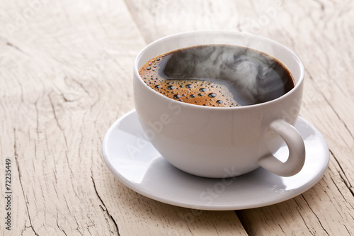 Foto op Canvas Koffie Cup of hot coffee on an old wooden table.
