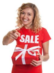 Blonde Frau im Sales-Shirt mit Geschenk zeigt zur Kamera
