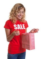 Lachende blonde Frau im Sale-Shirt schaut in Einkaufstasche