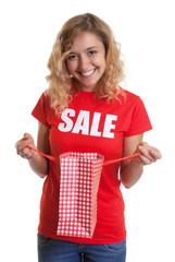 Blonde Frau im Sale-Shirt zeigt ihren Einkauf