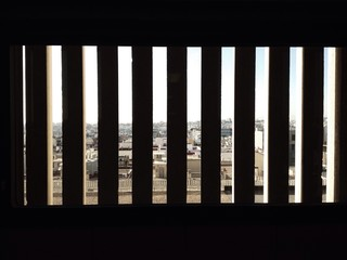 City behind a barred window in a jail