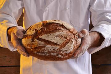 Panadero sujetando un pan grande.
