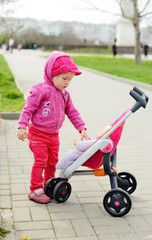 toddler with toy stroller