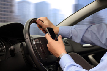 Businwssman using mobile smart phone while driving the car