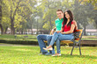 Young couple posing seated on a bench in park