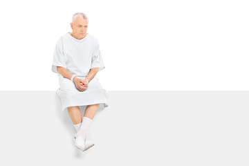 Worried mature patient sitting on a blank panel