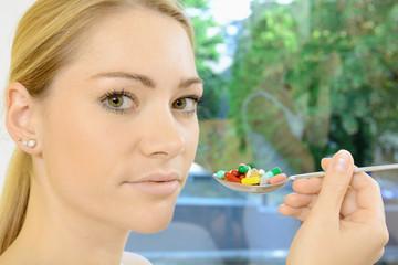 Frau mit Löffel voller Pillen und Tabletten