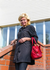 Blonde with a red handbag on the steps of the store