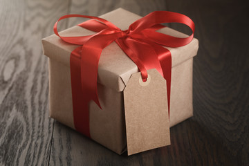 rustic gift box with red ribbon bow and empty tag
