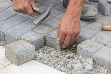 worker hands  laying concrete brick pavers 2