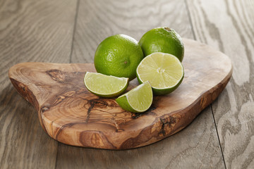 ripe limes on olive board