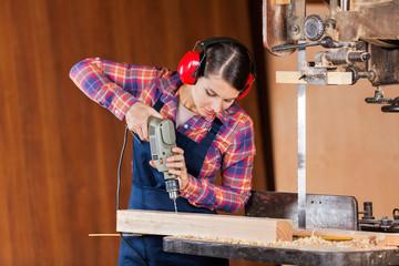 Carpenter Drilling Wood At Bandsaw