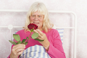 Happy female in bed with rose