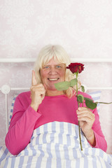 Happy woman in bed with rose