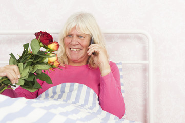 Smiling woman in bed with roses and telephone