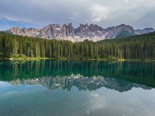 Latemar mountain and woods reflected in lake Carezza, Dolomites