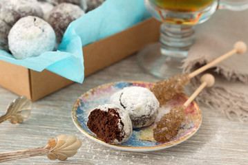 Chocolate homemade cookies in powdered sugar with tea