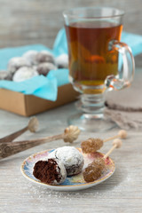 Chocolate cookies in powdered sugar with tea and caramel sugar