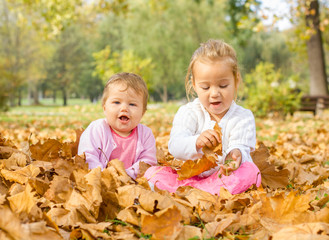 baby and little girl have fun with autumn leaves