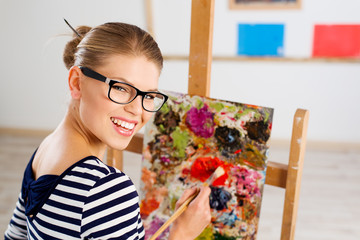 Young cheerful female painter creating new pictorial art.