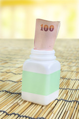 White pill bottle with Thai money note