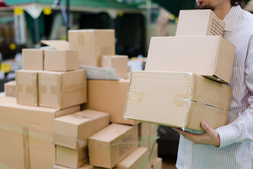 strong man holding, moving 3 boxes in the warehouse