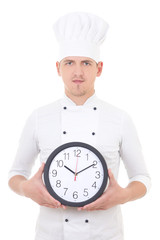 young man chef in uniform holding office clock isolated on white