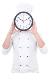 young man chef in uniform holding office clock behind his face i