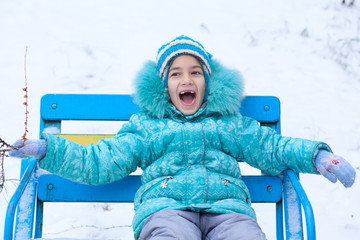 Happy kid girl child outdoors in winter sitting on bench