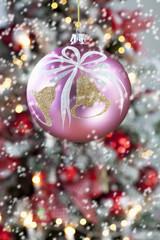Christbaumkugel vor geschmücktem Weihnachtsbaum, Nahaufnahme