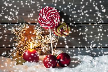 Weihnachtsdekoration auf Schneehaufen, Holzwand im Hintergrund