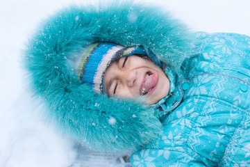 Happy kid lying on snow catching snowflakes with mouth