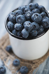 Close-up of an enameled cup with ripe blueberries, vertical shot