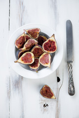 Sliced ripe figs in a plate over white wooden background