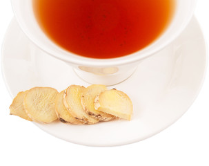 Ginger slices and a cup of tea over white background