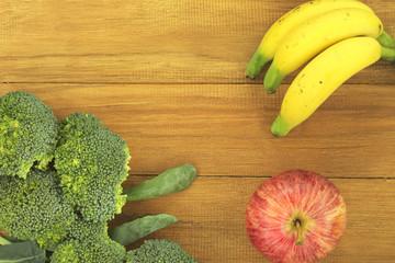 Broccoli, banana, and apple on golden teak wood background