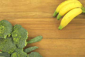 Broccoli and banana on golden teak wood background